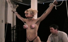 Naked female stands yielding and endures harsh sadomasochism